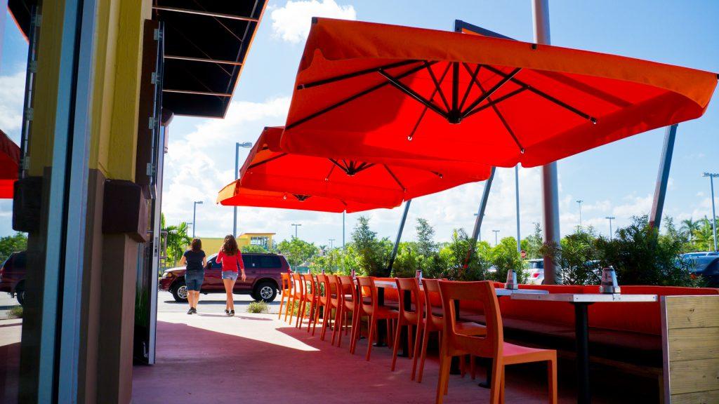 Parasol a pied déporté rouge Caravita chez Dupont Kine